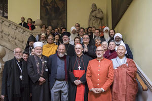 A group of religious leaders from around the world smiling and standing together for a photograph