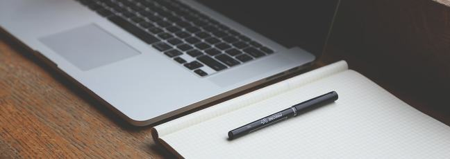 Writing a CV online: a laptop, notebook and pen on a desk