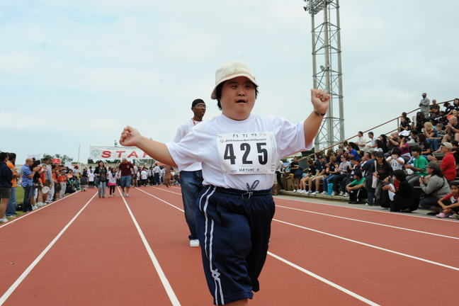 A child with Down Syndrome running in a race.