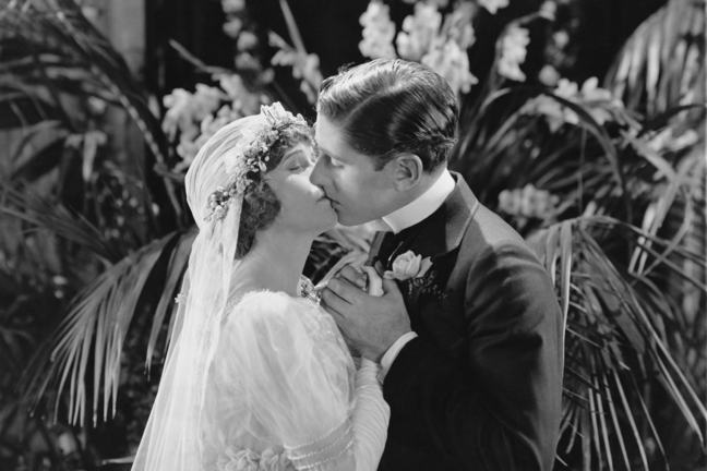 This black and white image shows a couple kissing on their wedding day