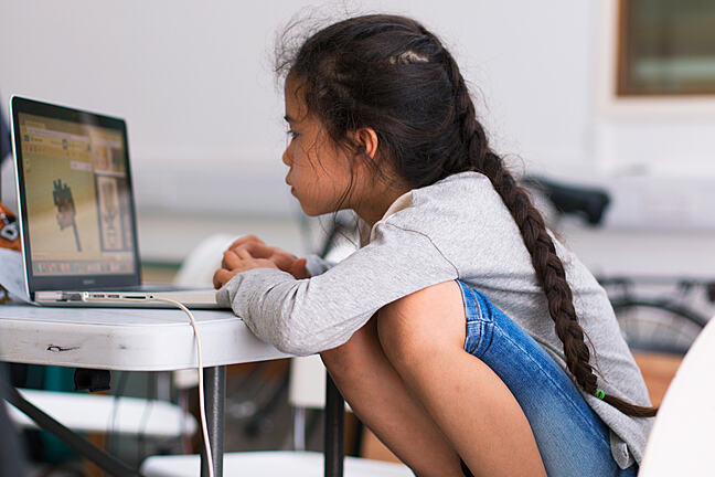 A photograph of a young girl programming on her own