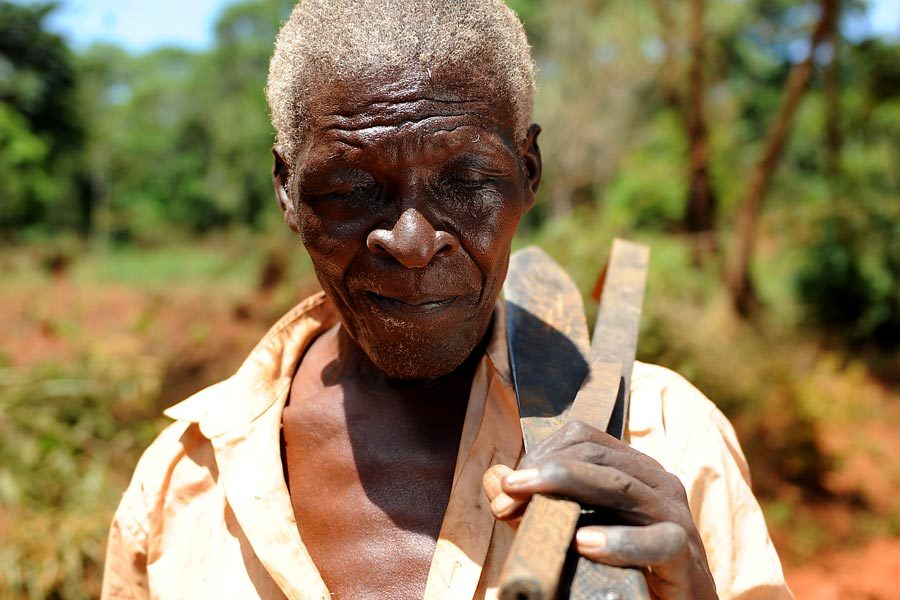 A visually impaired man carrying his farm tools.