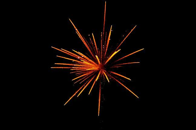 A firework in reds, yellows and oranges, set against a black sky.
