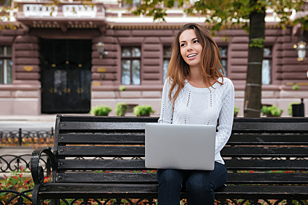 Smiling lovely young woman thinking and using laptop in park