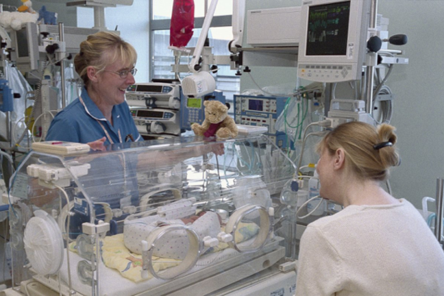 An image of a special care baby unit, showing two adults next to an incubator with a small baby. A teddy bear is on top of the incubator.