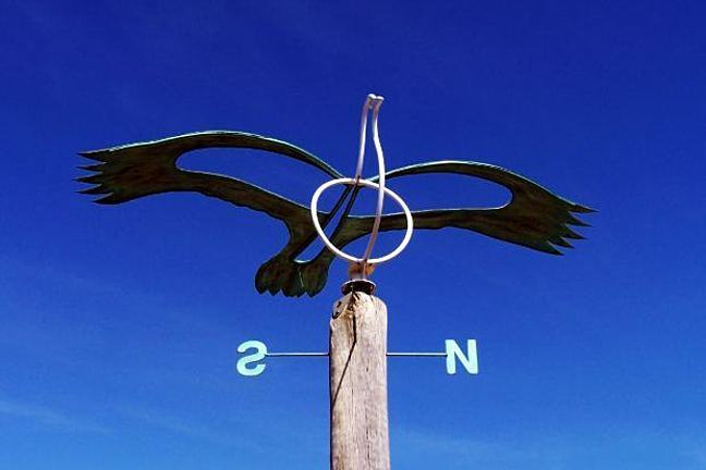 Weather vane with North and South directions visible