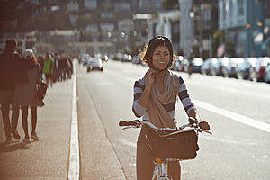 Women smiling and cycling down city street