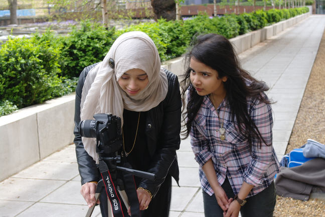 Two girls outside adjusting their camera on a tripod ready for filming