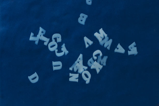 Image of the impressions of randomly scattered letters on a blue background