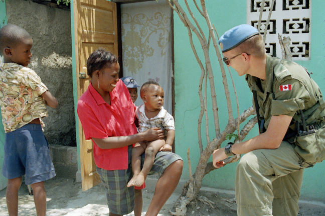 A group of UNSMIH peacekeeping soldiers from the Canadian Battalion stop to talk with a Haitian woman in Port-au-Prince.