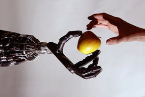 Human hand taking an apple from a robot hand