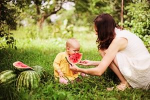 Mother and baby eating watermelon in natural bright surroundings