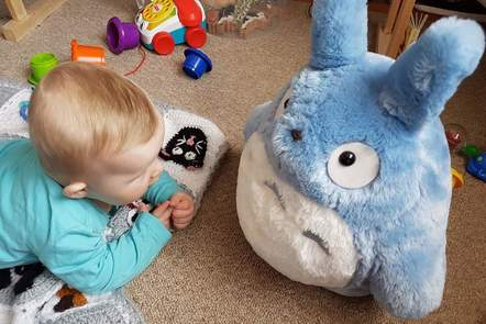 A baby plays with Totoro soft toy