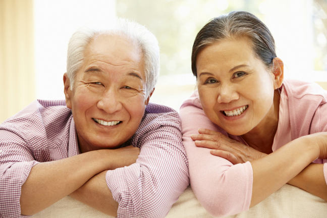 An image of an older man and woman smiling with their arms folded.