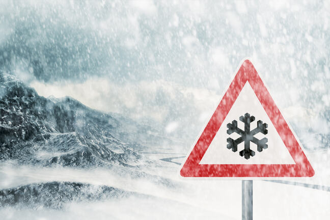 A traffic sign signalling snow, in a blizzard