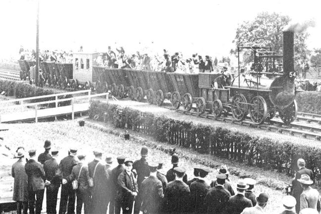 Black and white photograph of steam locomotive surrounded by crowds of people