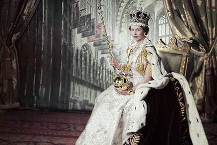 Photograph of Queen Elizabeth II, seated, after her coronation, wearing the Imperial State Crown and holding the Sovereign's Orb and Scepter with Cross, wearing the gold Armills, her floor-length coronation dress, and coronation robes.
