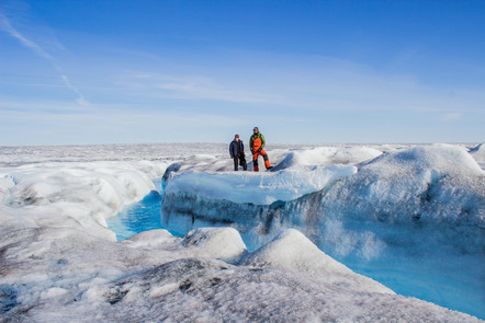 Two researchers stand on the Greenland Ice Sheet in 2016.