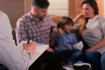 young child with parents on couch blurred in the background, psychologist in foreground with clipboard and pen