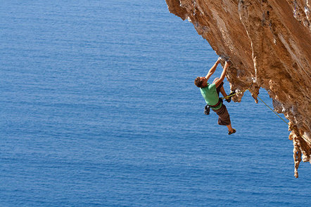 A man climbs up the side of a rock above the ocean.