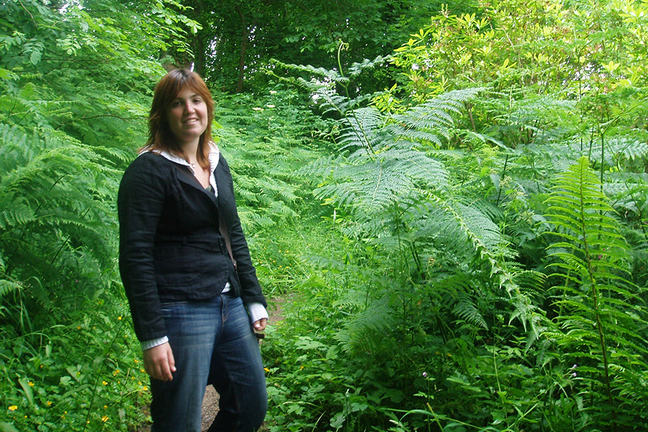 A photo of a young woman, casually dressed, standing in woodland amongst ferns and wild flowers.