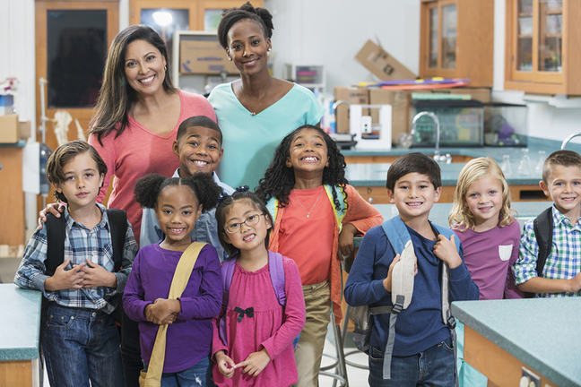 eight diverse school children standing with two teachers