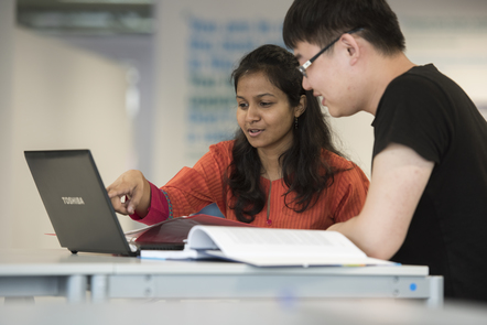 Two students studying with a laptop