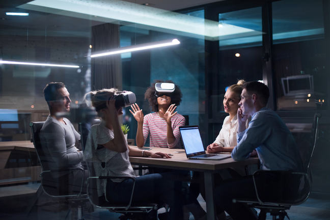 Business team sit around a meeting table experimenting with virtual reality technology