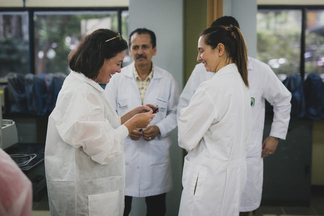 Four Educators in white laboratory coats, two women in the foreground laughing together, and set further back a man observing with another person partly hidden