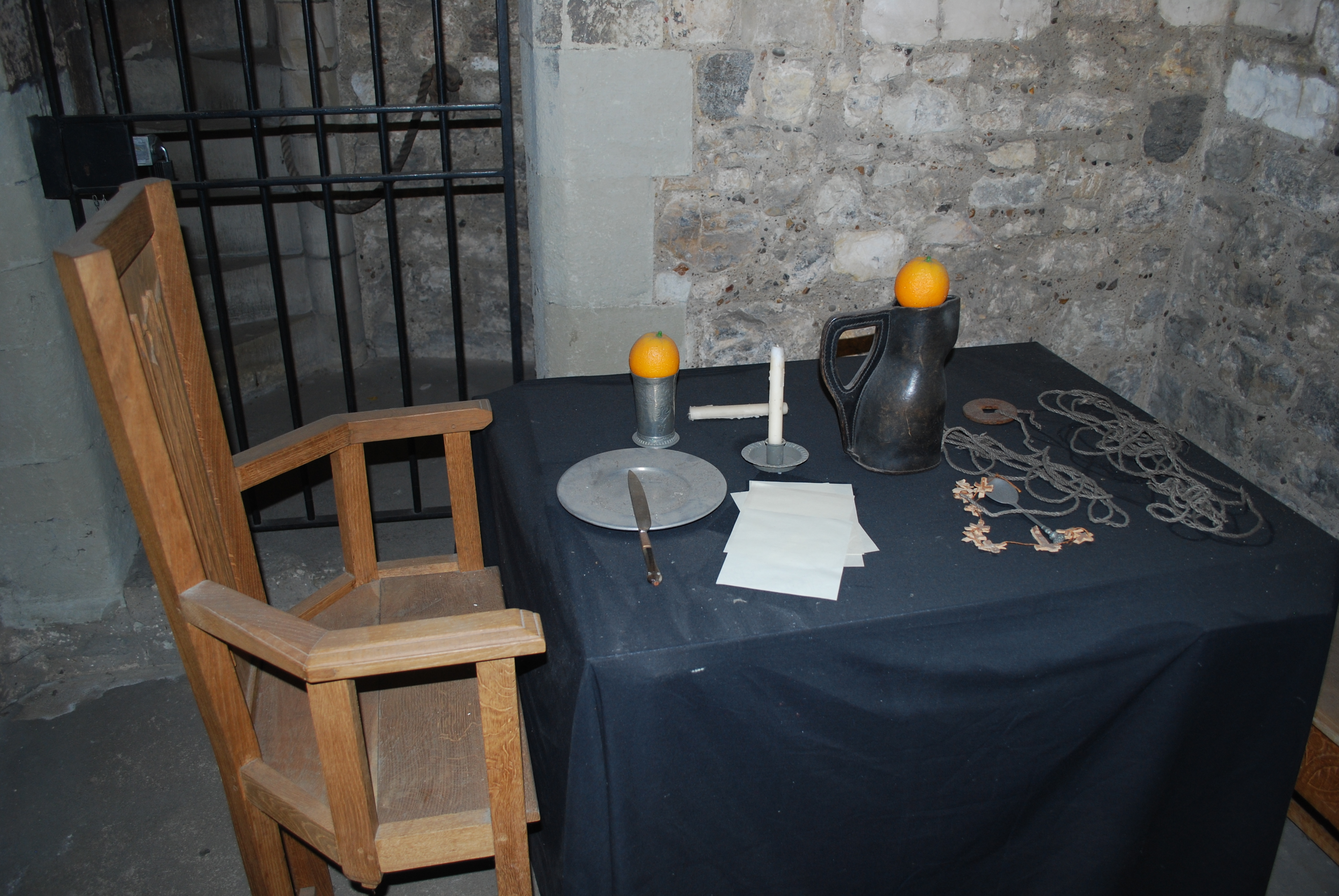 A photograph of a recreation within a cell: There is a small table with a navy table cloth and a wooden chair. On the table there is a plate, knife, 2 oranges, 2 candle sticks and a water jug.