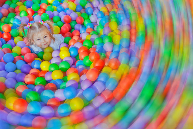Girl at centre of a ball pool