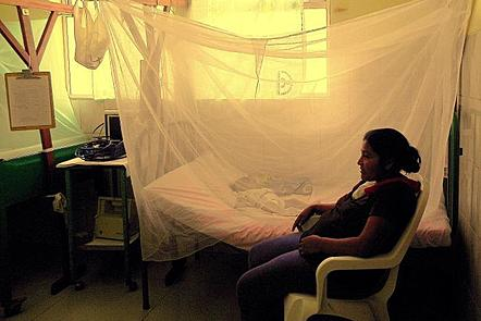 An adult woman sits on a white chair, next to a bed which is cloaked in an insecticide treated bed net. A child is sleeping under the net on the bed.