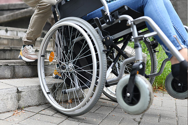 Close-up of a wheel chair being pulled backwards up steps