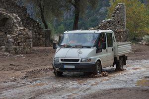 Pick up truck driving through muddy terrain.