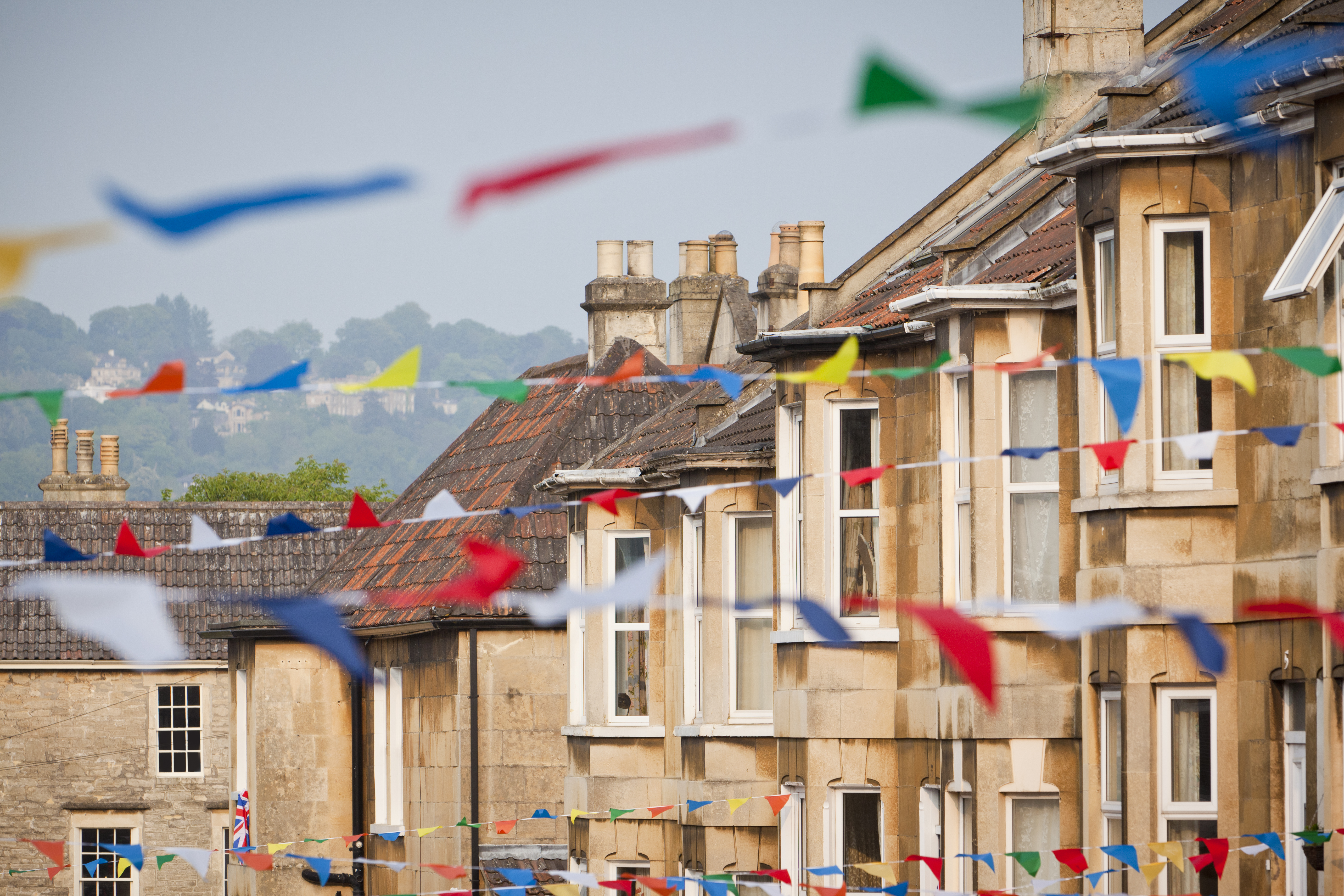 A row of houses with colourful bunting draped between each house.