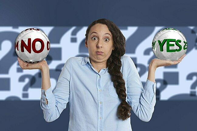Photo of a confused woman, holding a No ball and a Yes ball