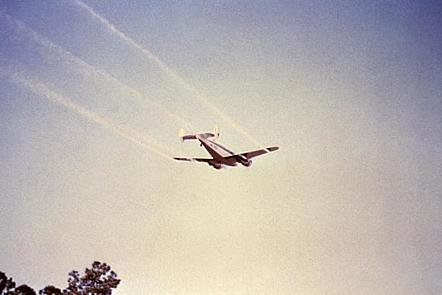 A twin engine aeroplane flying in the sky, releasing streams of white cloudy vapour insecticide.