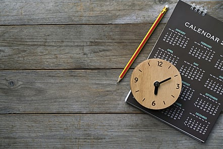 Close-up of a clock, calendar and pencil on the table.