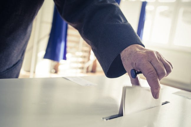 Photo of someone placing their voting paper into a voting box.