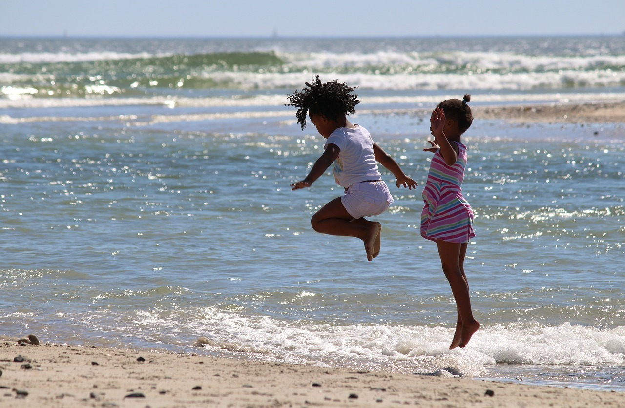 photograph of children jumping in the ocean