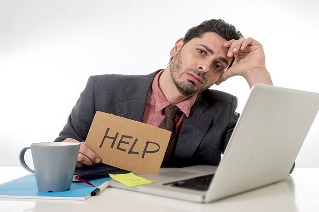 A business man who is bored at work holds up a sign handwritten on cardboard that says 'help'. In front of him sits a laptop computer and notebooks.