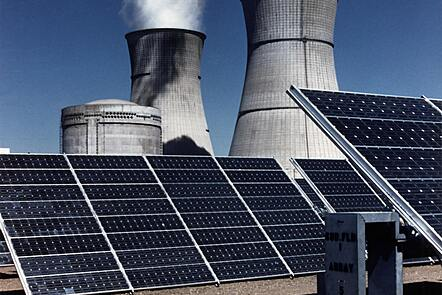Solar panels in front of industrial chimneys