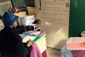 Two refugees, one male, one female sitting in a makeshift classroom looking at writing on a board