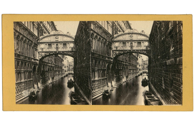 Stereocard depicting Bridge of Sighs, Venice, Italy, joining two buildings with a canal and canal boats below.