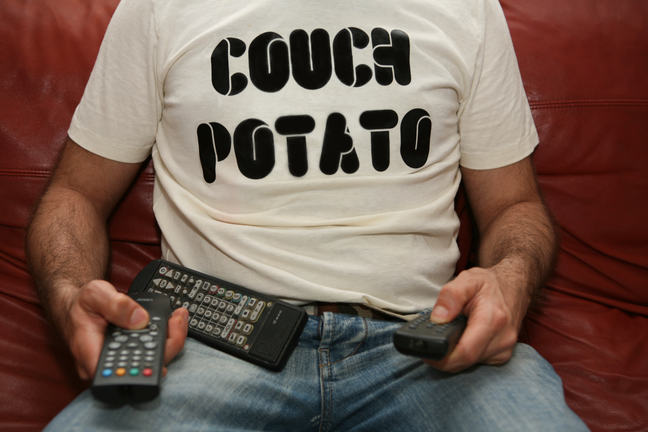 A man wearing a t-shirt reading 'couch potato' sits on a sofa holding remote controls