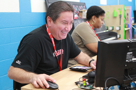 A photograph of an educator enjoying coding
