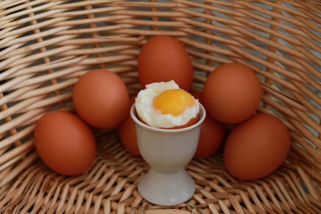 a soft boiled egg in a egg cup surrounded by other eggs in a basket