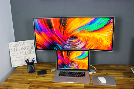 A wide curved computer monitor and a smaller laptop below it, both with the same image