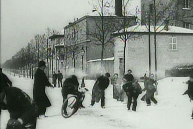 Black and white still image from Snowball Fight film scene - Louis Lumière c. 1895 - 1897. Group of people having a snowball fight in the street.