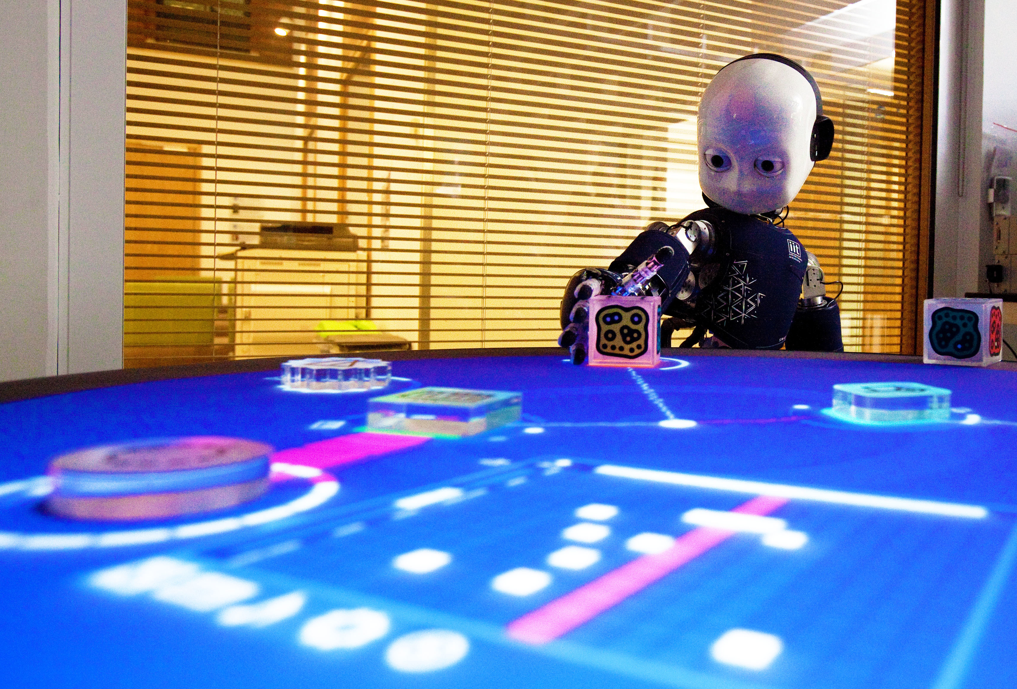 A child-like iCub robot plays a game where it learns how to match shapes to corresponding places on a light-up board